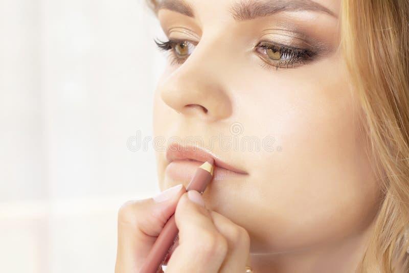 Makeup artysta stawia uzupełnia na dziewczyna modelu ślubny makeup, wieczór makeup, naturalny makeup makijażu artysta maluje warg obraz stock