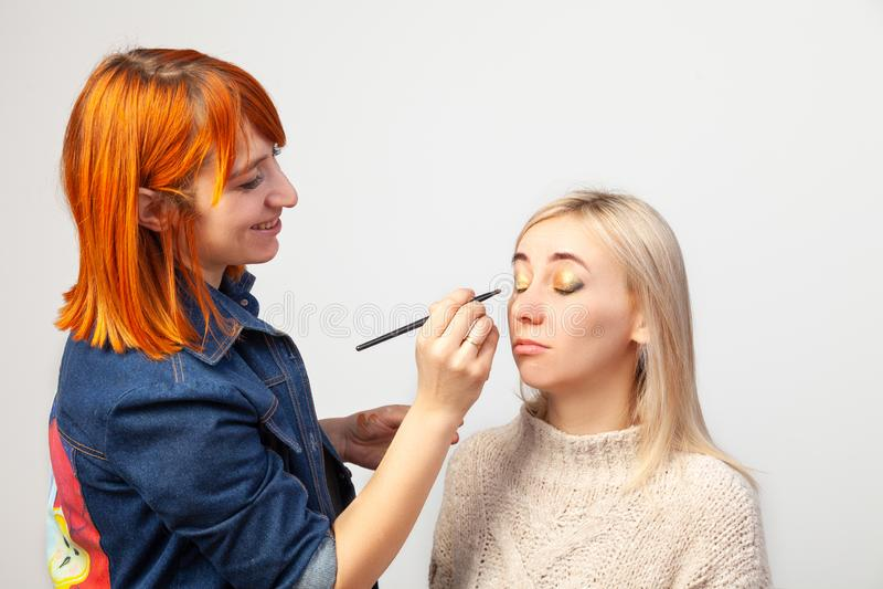 Makeup artysta stosuje makijaż blondynki dziewczyna z muśnięciem w jej ręce i stawiać złotych cienie zamknięte powieki obrazy stock