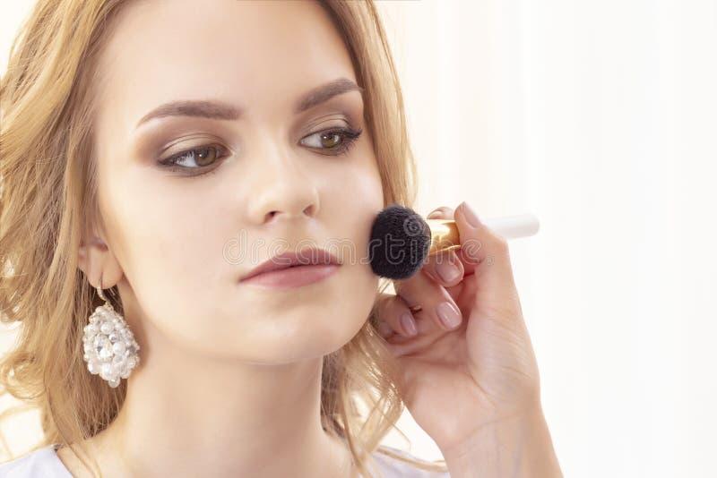 Makeup artysta stosuje pięknego modela proszek, rumiena z dużym muśnięciem na twarzy i zdjęcia stock