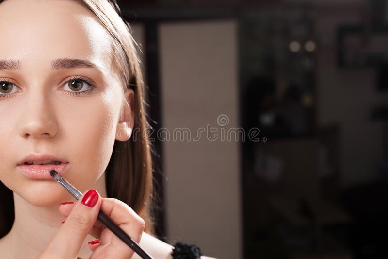Makeup artysta stosuje wargi glosę na nastoletnim zdjęcie royalty free