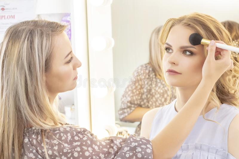 Makeup artysta stosuje wzorcowego makeup na twarzy bridal makeup, lekki wieczór makijaż w nagich brzmieniach zdjęcia stock