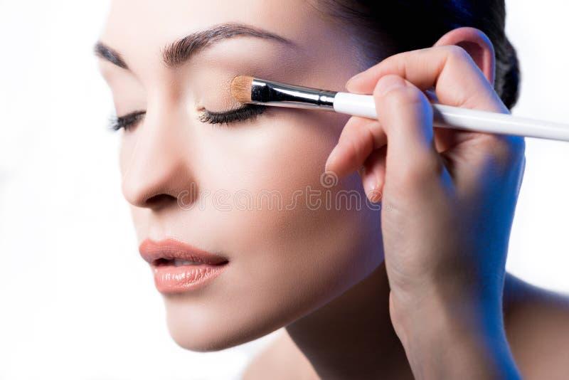 Makeup artysta używa muśnięcie stosować oko cień na twarzy kobieta zdjęcia royalty free