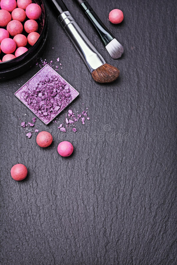 Makeup background on black slate. Makeup background with blush balls, eyeshadow and brushes on black slate royalty free stock image