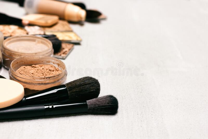 Makeup background. Make-up powder, foundation, concealer with brushes and cosmetic sponges on concrete surface with copy space stock images