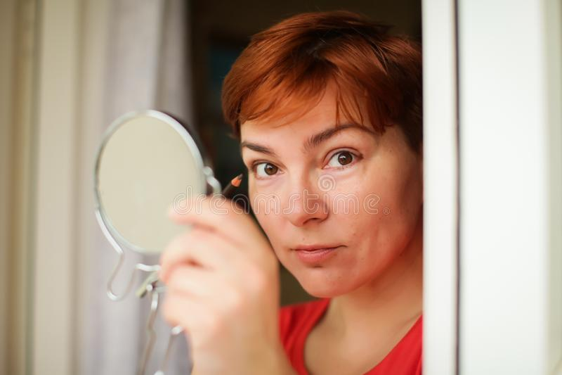 Makeup beauty care woman. Adult woman looks into mirror and putting eye pencil color on eyes royalty free stock images