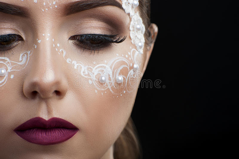 Makeup beauty shots. Pearly elegance. Cropped closeup of a young woman wearing creative bridal makeup with lace and pearls attachments royalty free stock images