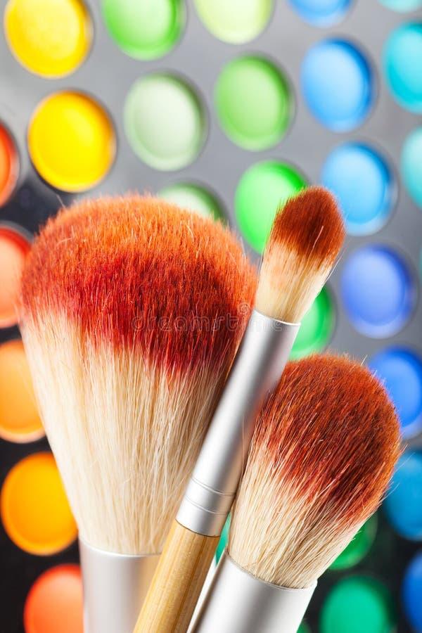 Makeup borstar, och uppsättningen av färgrikt synar skuggar som bakgrund arkivbilder