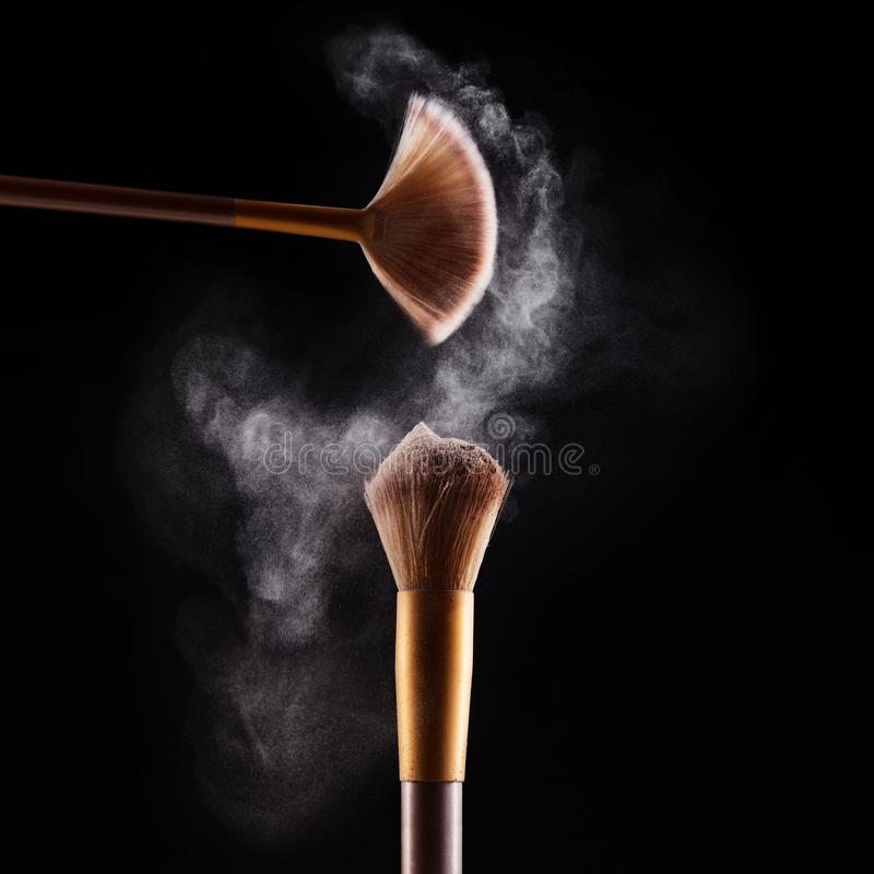 Makeup brush with blue powder explosion stock images
