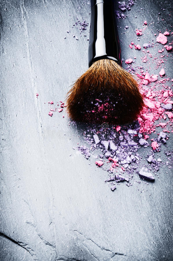 Makeup brush and crushed eye shadows stock photos