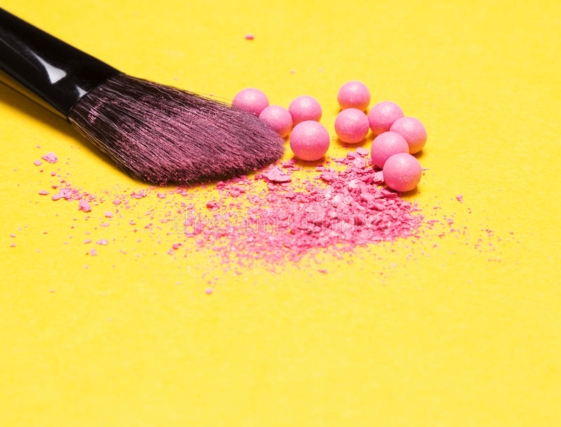 Makeup brush with crushed and whole shimmer blush balls. Close-up of makeup brush with crushed and whole shimmer blush balls pink color on yellow background stock photo
