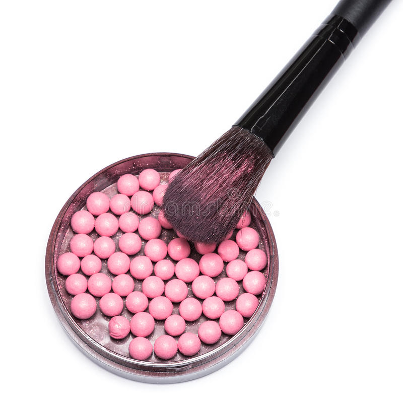 Makeup brush on jar with shimmer blush balls. Close-up of makeup brush lying on jar filled with shimmer blush balls pink color. White background stock photo