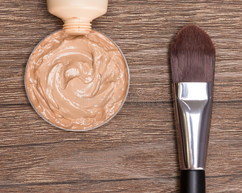 Makeup brush with liquid foundation squeezed out of tube. Close-up of flat makeup brush with liquid foundation squeezed out of tube on dark wooden surface royalty free stock images