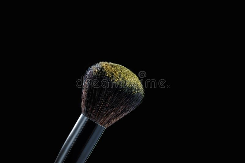 Makeup brush with powder on black background. Close-up of makeup brush with yellow eye shadow on black background stock photography
