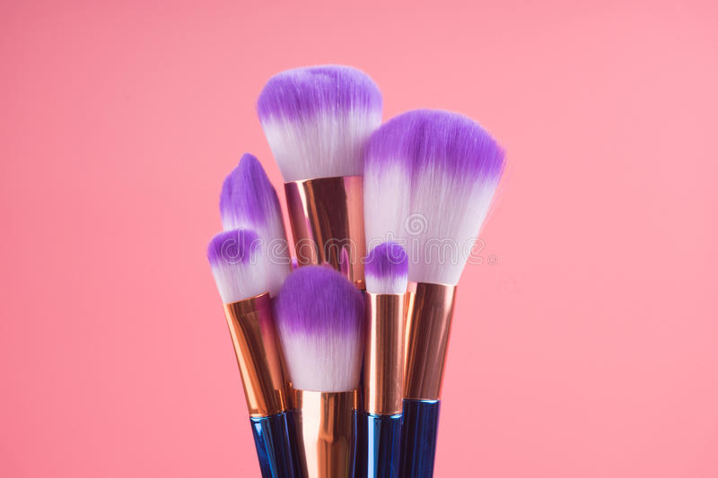Makeup brush set on red pink pastel background royalty free stock photography