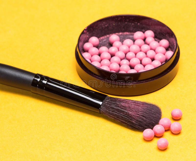 Makeup brush with shimmer blush balls. Close-up of makeup brush on the background of jar filled with shimmer blush balls pink color. Bright yellow background royalty free stock photography