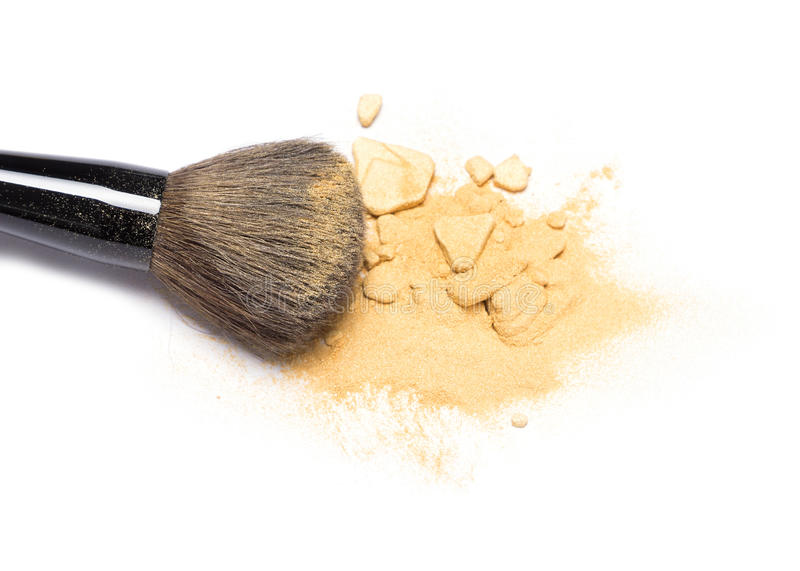 Makeup brush with shimmer powder golden color. Close-up of makeup brush with crushed mineral shimmer powder golden color on white background royalty free stock image
