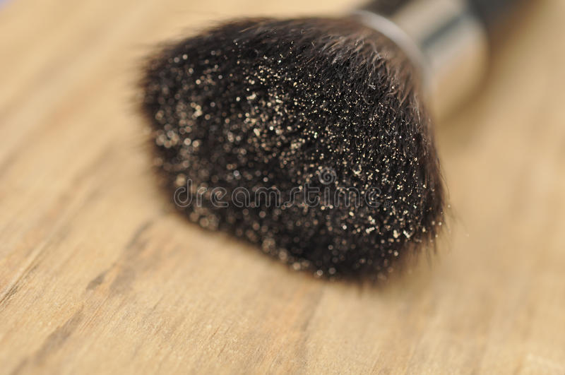 Makeup Brush With Shimmer Powder On Wood Table. Background stock photo