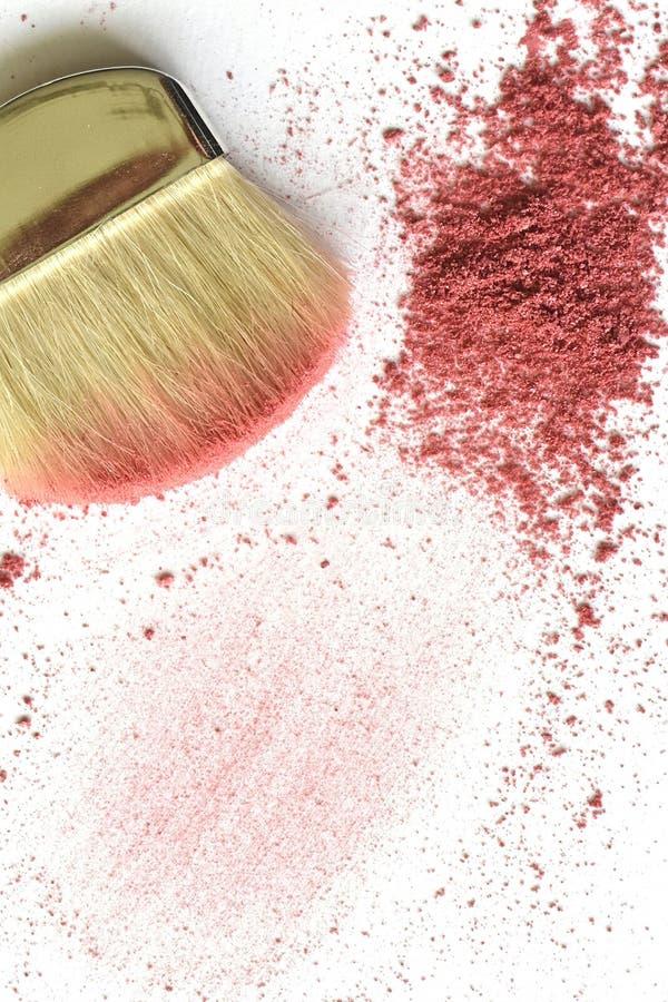 Loose pink powder and makeup brush on white royalty free stock photo