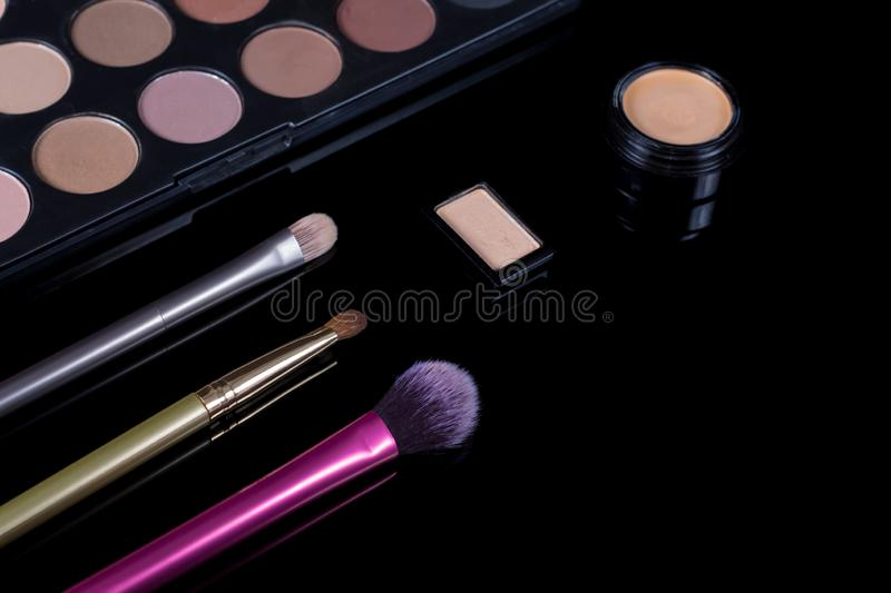 Makeup brushes on black background. Cosmetics, fashion, beauty, glamour. Accessories for make-up artist. Eyeshadow palette, stock photos