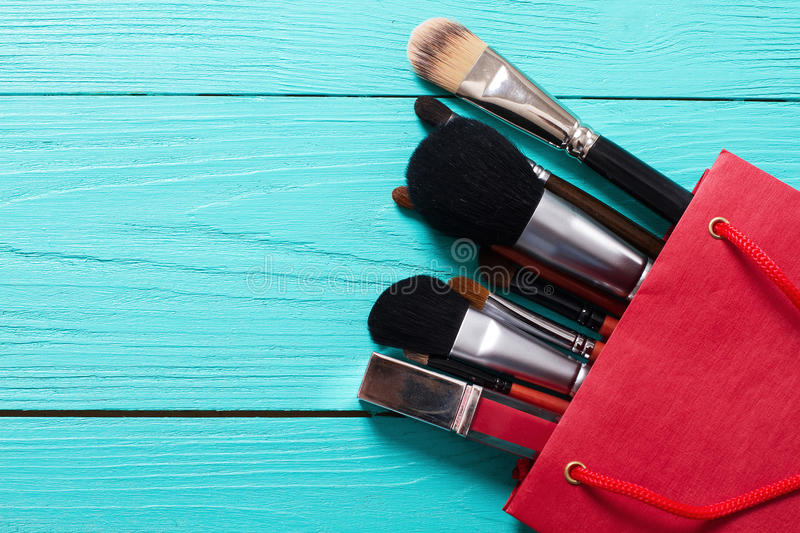 Makeup brushes on blue wooden background with copyspace. Make-up tools in red paper bag. Top view stock photos