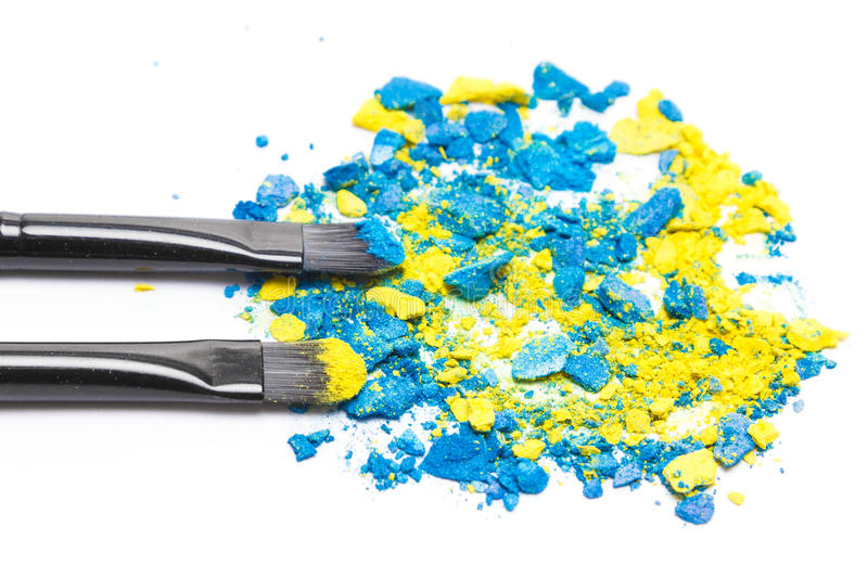 Makeup brushes with crushed compact blue and yellow eyeshadow stock images