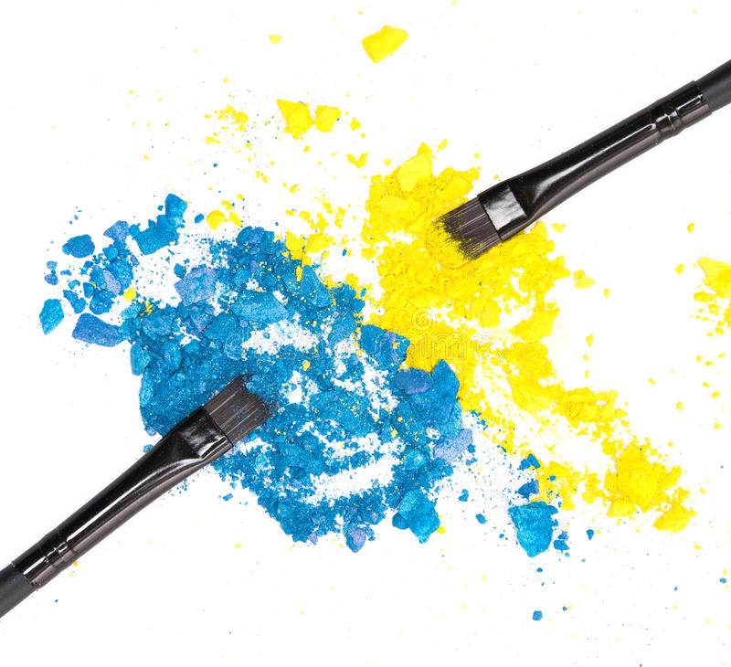 Makeup brushes with crushed compact blue and yellow eyeshadow stock photography
