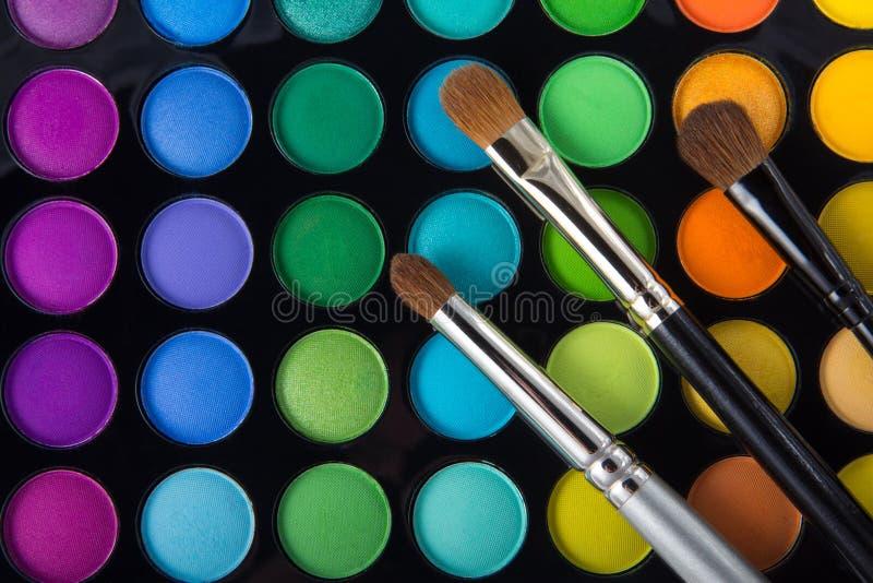 Makeup brushes and eye shadows stock photos