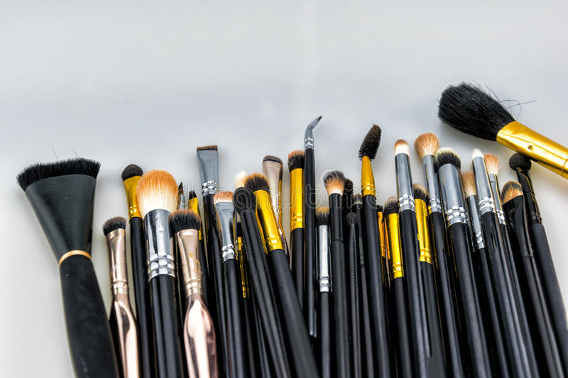 Makeup Brushes. Multitude of professional makeup brushes in different colors, forms and sizes isolated on neutral background royalty free stock photography