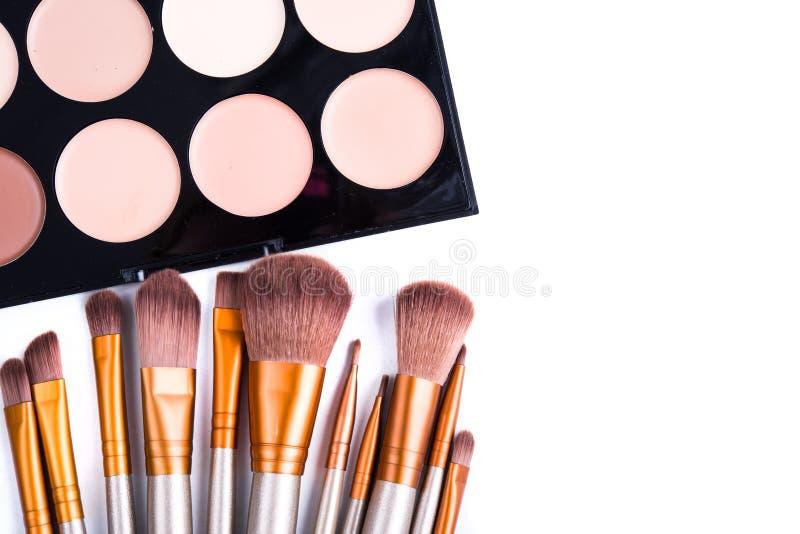 Makeup brushes set and foundation cream isolated. Makeup brushes set and foundation cream palette, beauty professional tools isolated on white background stock image