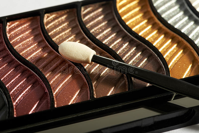 Makeup case with applicator. Close up view of compact makeup case with applicator on top of various eye shadow colors stock image