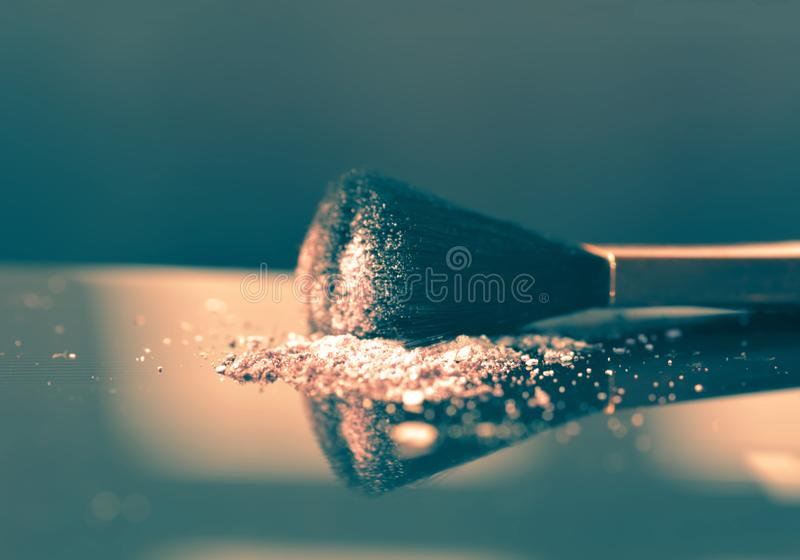 Makeup concept with a single professional makeup brush. With glowing face powder stock photo