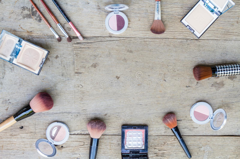 Makeup cosmetics. Cosmetics with powder and brush on wood table. Top view stock images