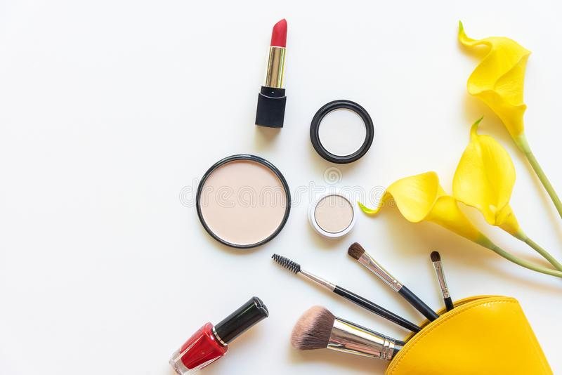 Makeup cosmetics tools and beauty cosmetics gift, products and facial cosmetics package lipstick with yellow flower on the white b royalty free stock image