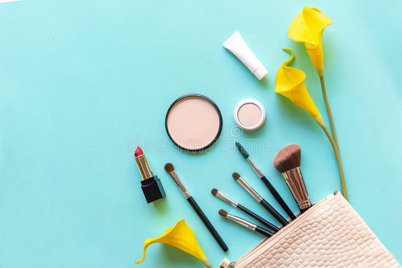 Makeup cosmetics tools and beauty cosmetics gift, products and facial cosmetics package lipstick with yellow lily flower on blue b stock photos