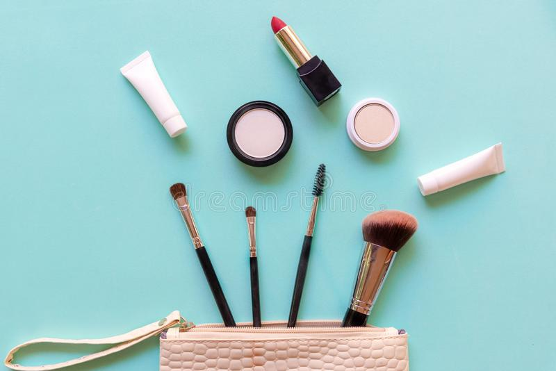 Makeup cosmetics tools and beauty cosmetics, products and facial cosmetics package lipstick, eye shadow on green pastel background royalty free stock image