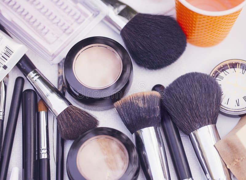 makeup of decorative cosmetic powder, concealer, eye shadow brush, blush, foundation, false eyelashes stock photo