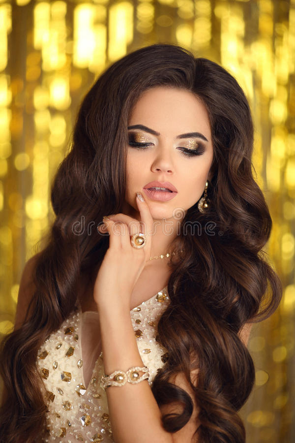 Makeup. Elegant brunette woman in gold. Fashion jewelry. Wavy ha. Ir style. Matte lips. girl model in golden dress with gold accessories over bokeh lights party royalty free stock photo