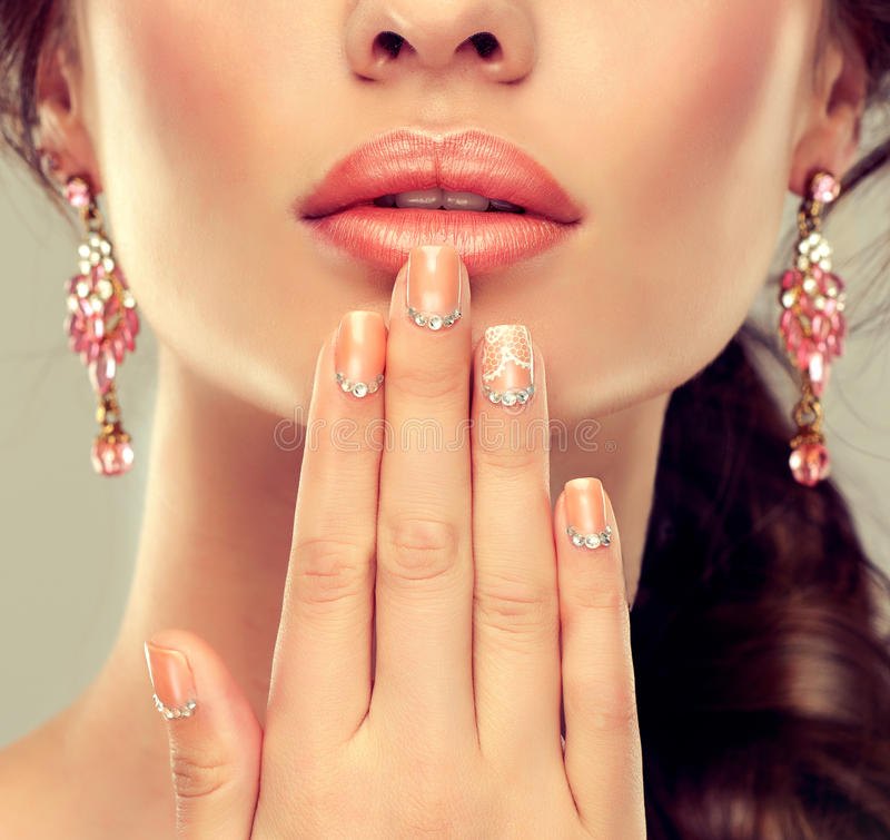Makeup for eyes and lips ,eyeliner and coral lipstick. Beige trend manicured nails with rhinestones stock image