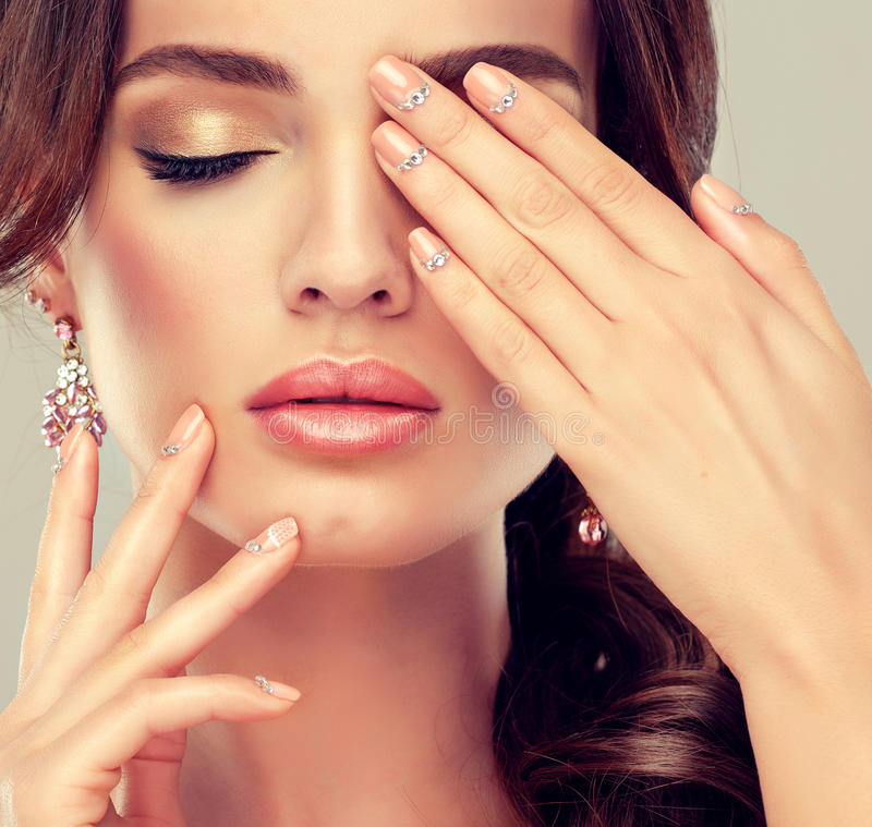 Makeup for eyes and lips ,eyeliner and coral lipstick. Beige trend manicured nails with rhinestones stock images
