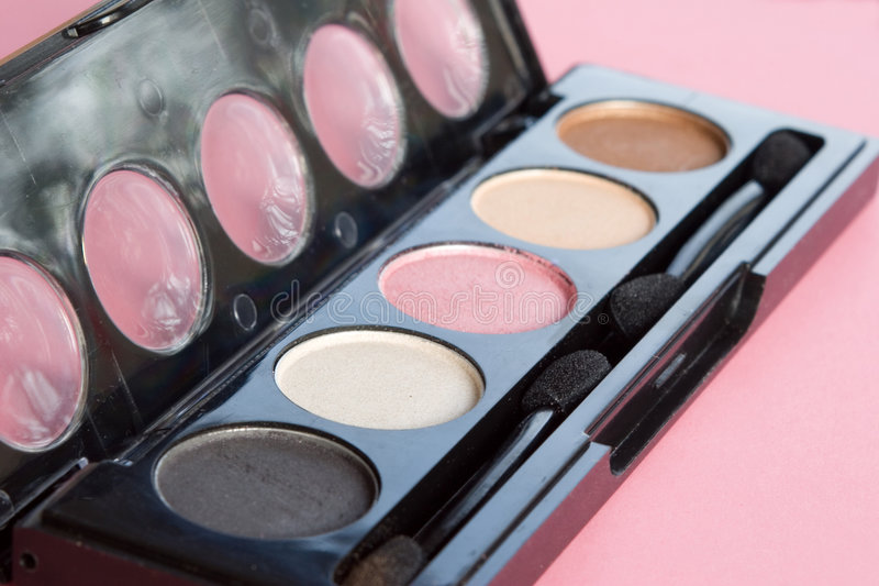 Makeup: eyeshadow in case with applicator. Makeup: eyeshadow in black case with applicators - close-up view stock photo