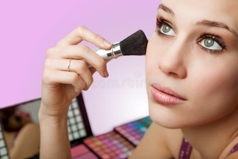makeup för rodnadborsteskönhetsmedel genom att använda kvinnan arkivbilder