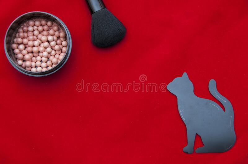Makeup flat lay on the red background. Face powder, makeup brush and stencil in the form of a cat for drawing eye lines. Beauty products royalty free stock image