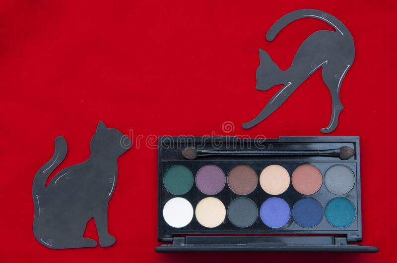 Makeup flat lay on the red background. Multicolored eye shadow and stencils in the form of a cat for drawing eye lines. Beauty products stock image