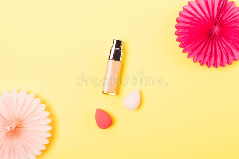 Makeup foundation cream next to egg. Shaped sponge applicators and festive tissue paper decorations on yellow background, flat lay stock image