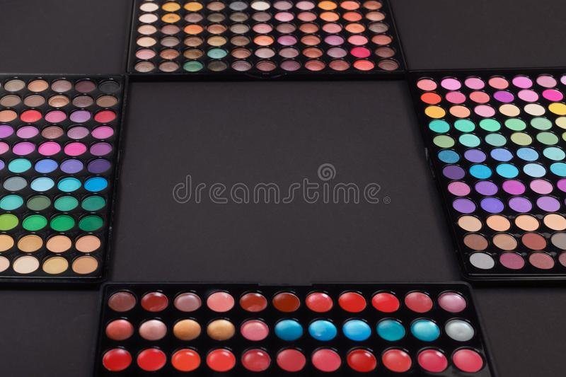 Makeup frame made of eyeshadow palettes on black. Background royalty free stock photos