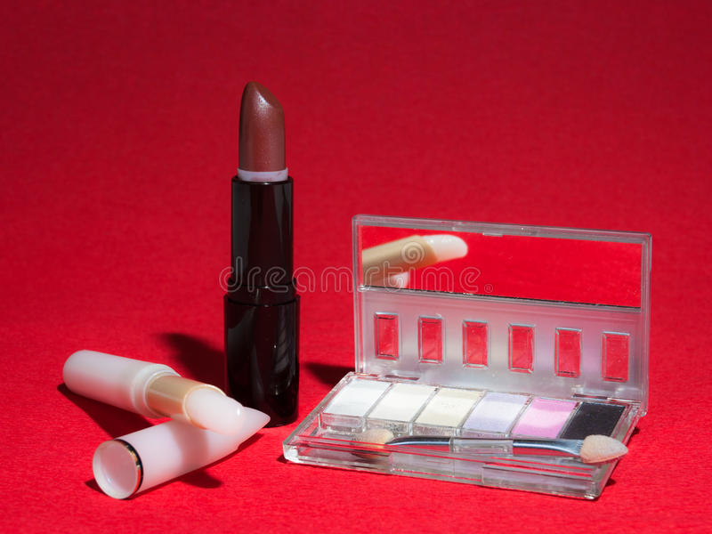 Makeup items on red background with high-contrast lighting. Cosmetics including lipstick, lip gloss and an eye shadow compact with mirror and small brush royalty free stock image