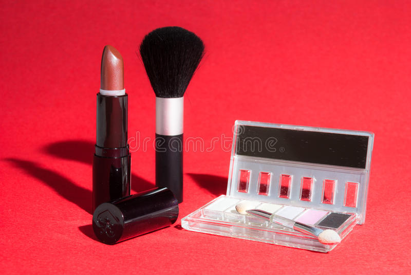 Makeup items on red background with high-contrast lighting. Cosmetics including lipstick, a powder brush and an eye shadow compact with brush photographed on a royalty free stock image