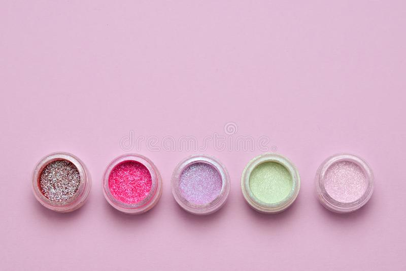 Makeup. Jars with crumbly bright shadows, glitter. P. Cosmetics. Makeup. Jars with crumbly bright shadows, glitter. Pink, green, lilac colors on lilac background royalty free stock photos