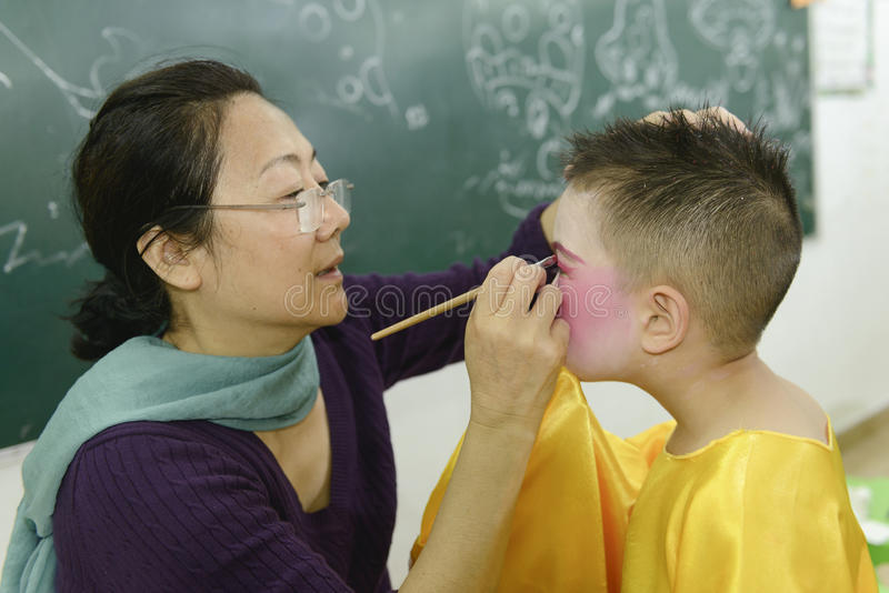 Makeup for kid. Chinese teacher makeup for kid on childrens day in classroom royalty free stock photos