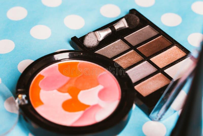 Makeup kosmetyki na błękitnym drewnianym stole i muśnięcie fotografia royalty free